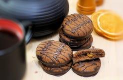 Biscuits de chocolat et ustensiles de thé noir Tasse et théière Parts oranges sèches Scène de thé photos stock