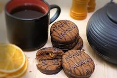 Biscuits de chocolat et ustensiles de thé noir Tasse et théière Parts oranges sèches Scène de thé photographie stock libre de droits