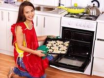 Biscuits de cuisson de fille dans le four photo libre de droits