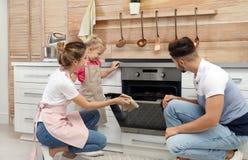 Biscuits de cuisson de famille heureuse en four photo libre de droits