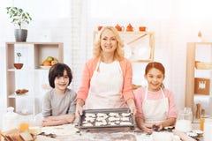 Biscuits de cuisson La belle grand-mère avec ses petits-enfants font des biscuits cuire au four dans la cuisine Image libre de droits