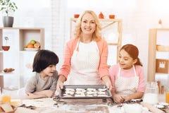Biscuits de cuisson La belle grand-mère avec ses petits-enfants font des biscuits cuire au four dans la cuisine Images stock