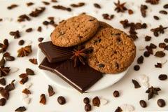 Biscuits de farine d'avoine avec du chocolat sur la soucoupe blanche sur le fond blanc Images stock