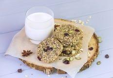 Biscuits de farine d'avoine avec les fruits secs, graines, canneberges Sur le fond gris en bois avec un verre de lait chaud frais image libre de droits