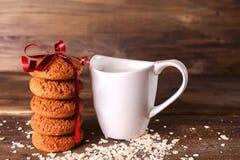 Biscuits de farine d'avoine sur un fond d'avoine, à côté d'un verre de lait, sur le panneau de vintage Images libres de droits