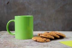 Biscuits de farine d'avoine sur une table et un verre vert Photographie stock libre de droits