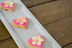 Biscuits de forme de coeur dans le plateau sur la planche en bois Images stock