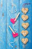 Biscuits de forme de coeur et deux coeurs de papier rouges sur le fond bleu Images stock
