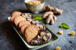 Biscuits de gingembre décorés du chocolat et des morceaux de gingembre glacé Images stock