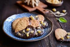 Biscuits de gingembre décorés du chocolat et des morceaux de gingembre glacé Image stock