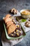 Biscuits de gingembre décorés du chocolat et des morceaux de gingembre glacé Photo stock