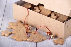 Biscuits de gingembre dans une boîte et à côté d'une boîte de biscuits Photos libres de droits