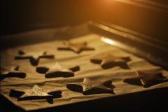Biscuits de Noël faisant cuire au four en four Étoiles de biscuits Image stock