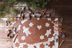 Biscuits de Noël de traitement au four Déroulez la pâte pour couper des étoiles et le gingerbreadman sur un fond en bois Photo stock