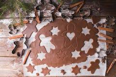 Biscuits de Noël de traitement au four Déroulez la pâte pour couper des étoiles et le gingerbreadman sur un fond en bois Photographie stock libre de droits