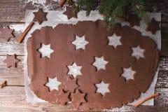Biscuits de Noël de traitement au four Déroulez la pâte pour couper des étoiles sur un fond en bois Photos libres de droits