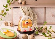 Biscuits de Pâques avec le lapin de Pâques, les oeufs de pâques et le poulet peints près du buffet et de la serviette décoratifs photos stock