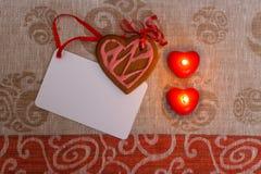 Biscuits de pain d'épice de chocolat en forme de coeur avec le glaçage rouge et rose et le ruban rouge après sur le tissu coloré Photographie stock