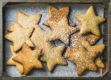 Biscuits de pain d'épice de Noël dans la forme des étoiles avec la poudre de sucre Images stock