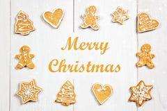 Biscuits de pain d'épice de Noël de différentes formes sur une table en bois blanche Joyeux Noël photographie stock libre de droits