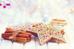Biscuits de pain d'épice de Noël et bâtons de cannelle sur la table en bois blanche Photographie stock libre de droits