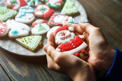 Biscuits de pain d'épice pour Noël, nouvelle année dans des mains d'enfants sur la table en bois Pâtisserie de fête et douce, bis photo stock