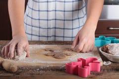Biscuits de pain d'épice de traitement au four Fermez-vous des mains du ` s de fille image libre de droits