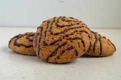 Biscuits de raisin sec de farine d'avoine avec des wawes de chocolat sur la table blanche photographie stock