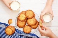 Biscuits de s?same avec du lait pour le petit d?jeuner pour des enfants Mains du ` s d'enfants dans le cadre Les enfants mangent  image stock