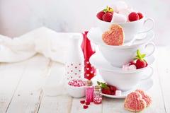 Biscuits de sucre de jour de valentines dans des tasses empilées Photographie stock