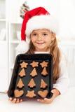 Biscuits de traitement au four de fille de Noël heureux Images stock