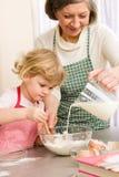 Biscuits de traitement au four de grand-mère et de petite-fille Photo libre de droits