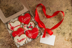 Biscuits de Valentine dans une boîte avec le ruban rouge et le papier vide blanc Photographie stock