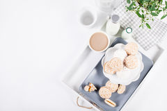 Biscuits doux sur le plateau blanc avec des bouteilles de lait et de fleurs pour Image stock