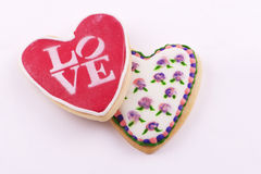 Biscuits en forme de coeur avec des fleurs dessinées et l'amour de mot Photos stock