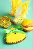 Biscuits en forme de coeur avec des sucreries sur le fond vert Images stock