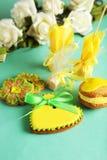 Biscuits en forme de coeur avec des sucreries sur le fond vert Photographie stock libre de droits