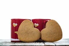 Biscuits en forme de coeur avec des tasses Photos stock