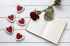 Biscuits en forme de coeur avec le cadre de carnet et la composition vides en cadeau de rose de rouge pour le jour de valentines Image stock