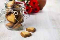 Biscuits en forme de coeur dans un pot en verre et des roses rouges Photographie stock