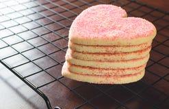 Biscuits en forme de coeur empilés de jour de valentines sur le support de refroidissement Photos stock