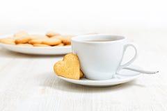 Biscuits en forme de coeur et une tasse de thé Photos libres de droits