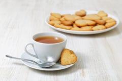 Biscuits en forme de coeur et une tasse de thé Photographie stock libre de droits