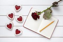 Biscuits en forme de coeur faits maison avec la composition vide en cadeau de cadre, de crayon et de rouge de rose de carnet pour Photos stock