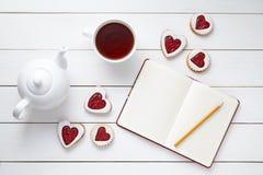 Biscuits en forme de coeur faits maison avec le carnet vide, le crayon, la tasse de thé et la théière sur le fond en bois blanc Image stock