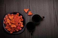 Biscuits en forme de coeur rouges d'un plat noir, deux tasses de café, vue supérieure Photographie stock libre de droits