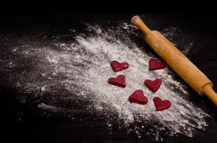 Biscuits en forme de coeur rouges sur une farine, faisant le jour cuire au four de la Saint-Valentin Photo stock