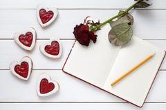Biscuits en forme de coeur sablés avec le carnet vide, le crayon et la fleur rose sur le fond en bois blanc pour des valentines Photo stock