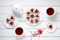 Biscuits en forme de coeur sablés pour le jour de valentines avec la théière et deux tasses de thé sur le fond en bois blanc bake Image libre de droits