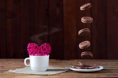 Biscuits en vol et une tasse de thé chaud, plan rapproché sur une étiquette en bois Images stock